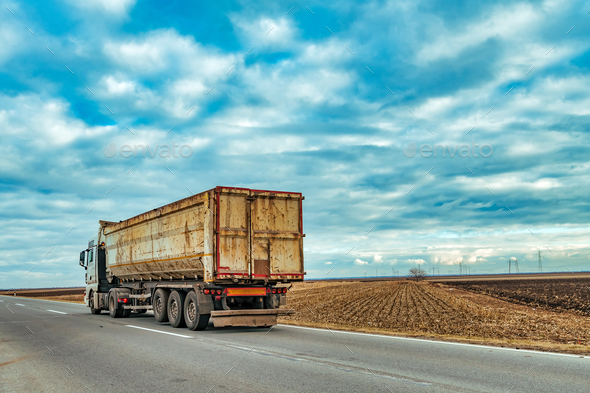 Truck on the road through countryside - Stock Photo - Images