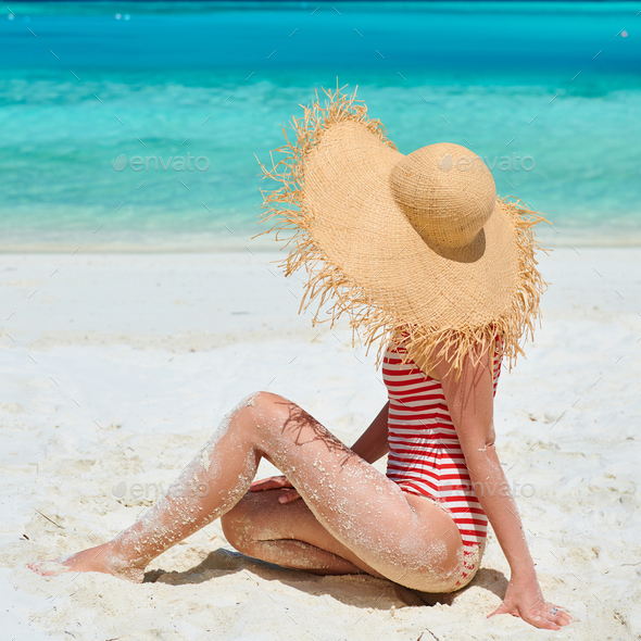 Woman in one-piece swimsuit at beach - Stock Photo - Images