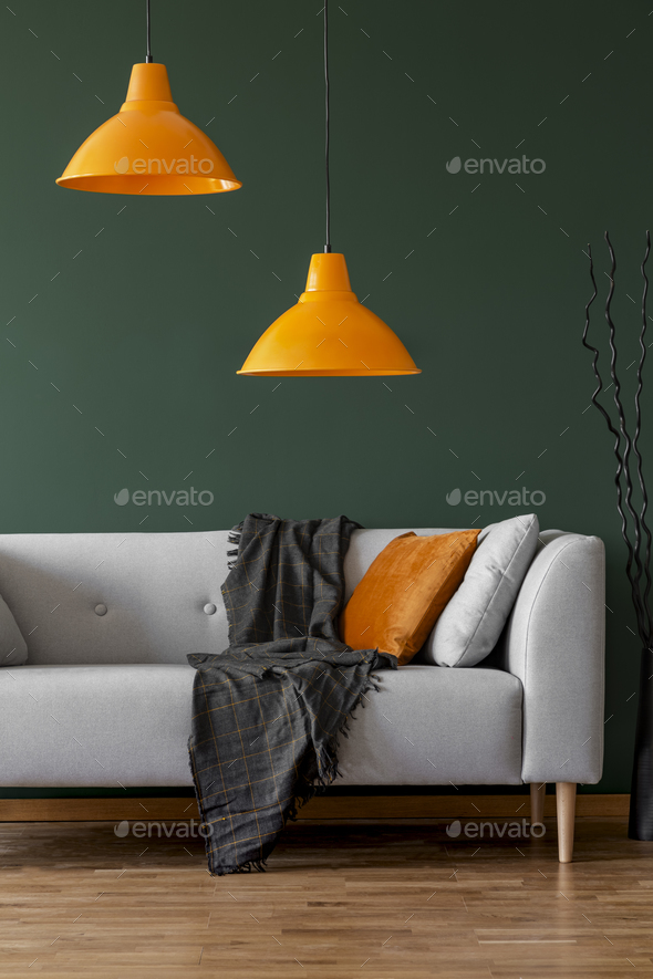 Orange lamps on a green wall and sofa in a simple living room interior