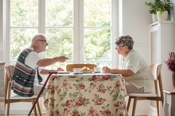 Senior couple sitting together at table drinking tea and eating cake - Stock Photo - Images