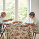 Senior couple sitting together at table drinking tea and eating cake - PhotoDune Item for Sale