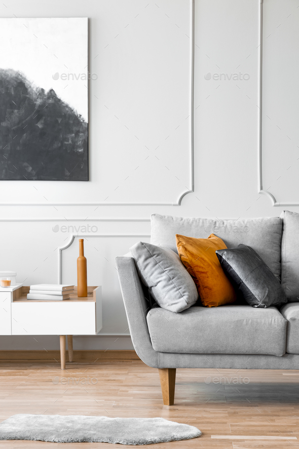 Poster above cabinet next to couch with pillows in grey living room interior with fur. Real photo - Stock Photo - Images