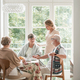 Group of senior friends with helpful carer sitting together at the table at nursing home dining room - PhotoDune Item for Sale