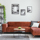 Black and white gallery of photos above brown velvet corner sofa - PhotoDune Item for Sale