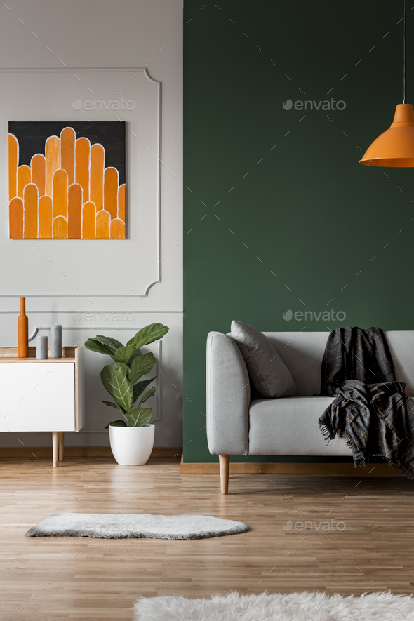Dark green wall in grey and orange living room interior