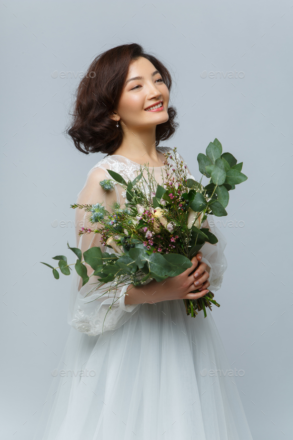 beautiful girl in white dress with big bouquet - Stock Photo - Images