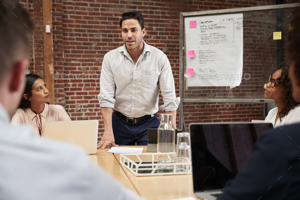 Mature Businessman Standing And Leading Office Meeting Around Table - Stock Photo - Images