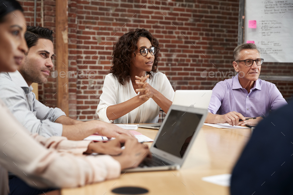 Businesswoman Leading Office Meeting Of Colleagues Sitting Around Table - Stock Photo - Images