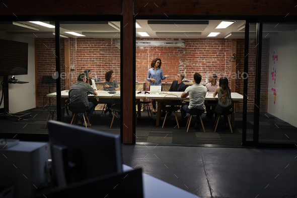 Business Team Having Late Night Meeting Sitting Around Boardroom Table - Stock Photo - Images
