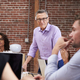 Mature Businessman Standing And Leading Office Meeting Of Colleagues Sitting Around Table - PhotoDune Item for Sale