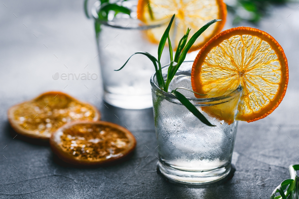 Two shots of cocktails with ice, dried orange slice and fresh tarragon on a grey table. - Stock Photo - Images
