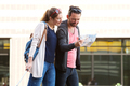 Couple walking in city with suitcases studying tourist map - PhotoDune Item for Sale