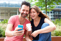 Close up happy young couple sitting together with mobile phone and coffee - PhotoDune Item for Sale