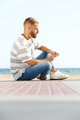 young man sitting on ground and listening to music with earphones - PhotoDune Item for Sale