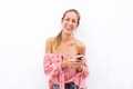 Smiling young woman with cellphone against white backgorund - PhotoDune Item for Sale