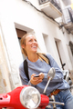 happy young woman sitting on scooter with mobile phone - PhotoDune Item for Sale