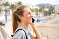 Side smiling young woman talking on mobile phone at the beach - PhotoDune Item for Sale