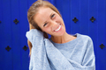 Close up smiling young woman against blue background - PhotoDune Item for Sale