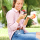 young woman sitting in park eating an apple and sending text message on mobile phone - PhotoDune Item for Sale