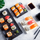Various Fresh and delicious sushi set on black and white slate with metal and slate sticks, sauce - PhotoDune Item for Sale