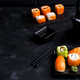 Asian food background with black iron teapot and sushi set on slate plate on black stone table - PhotoDune Item for Sale