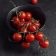 bunch of tomatoes on branch on textured black base - PhotoDune Item for Sale