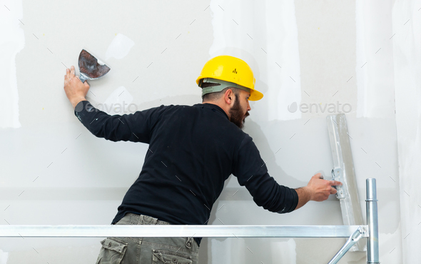worker plastering gypsum board wall. - Stock Photo - Images