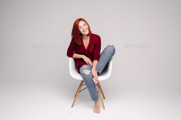 Model with ginger hair sitting on white chair in studio - Stock Photo - Images
