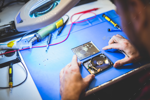 Worker fixing HDD disc in workshop. - Stock Photo - Images