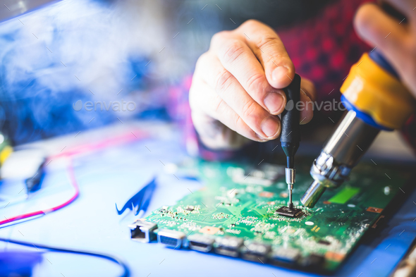 Worker fixing a main board of a computer. - Stock Photo - Images