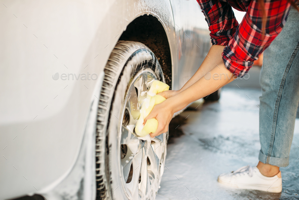 Cute woman scrubbing vehicle wheel with foam - Stock Photo - Images