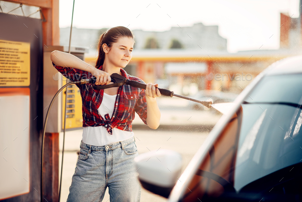 Young woman on self-service car wash - Stock Photo - Images