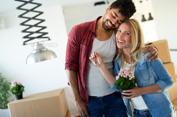 Young couple Moving in new home and unpacking carboard boxes - Stock Photo - Images
