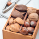Hazelnut, walnut, almond and brazil nuts in the wooden box with nut cracker - PhotoDune Item for Sale