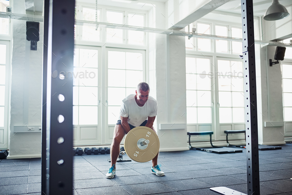 Senior man straining while lifting weights at a gym - Stock Photo - Images