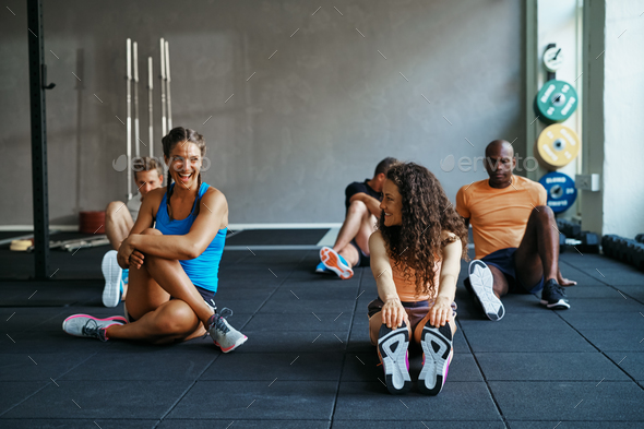 People talking together on a gym floor after working out - Stock Photo - Images