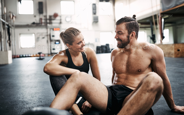 Fit couple smiling and talking during a break from exercising - Stock Photo - Images
