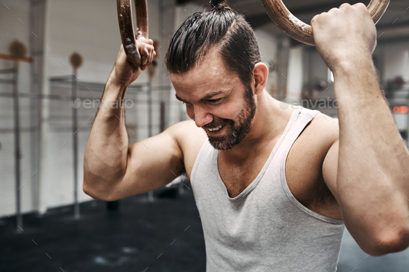 Smiling young man exercising with rings at the gym - Stock Photo - Images