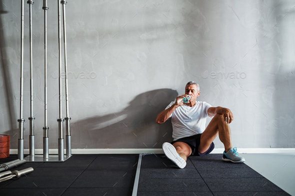 Mature man drinking water after a gym workout - Stock Photo - Images