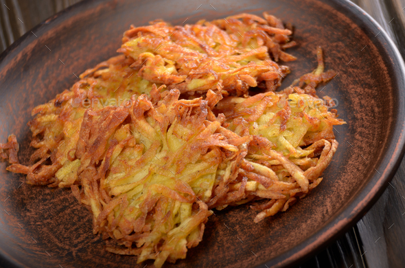 Fresh homemade tasty potato pancakes in clay dish on rustic wood - Stock Photo - Images