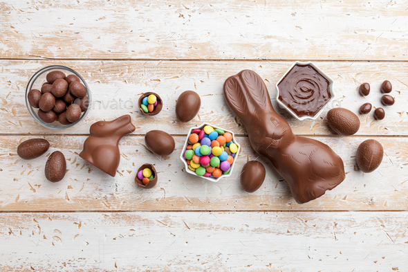 Chocolate Easter bunny, eggs and sweets on rustic background - Stock Photo - Images