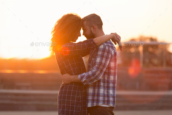 Beloved couple embracing and touching their foreheads at sunset - Stock Photo - Images