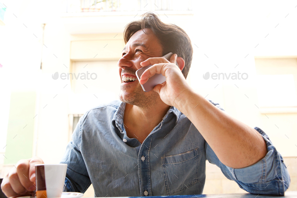 cheerful mature man talking on mobile phone at coffee shop - Stock Photo - Images