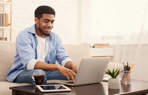 Millennial black man working on laptop in home office - Stock Photo - Images