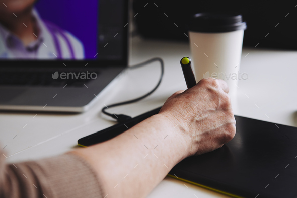 Woman designer working at a laptop with a graphics tablet - Stock Photo - Images