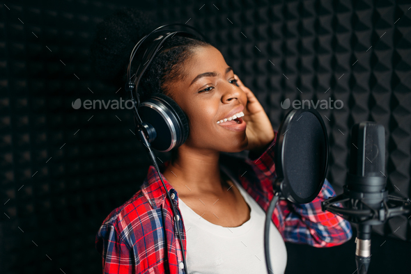 Female singer songs in audio recording studio - Stock Photo - Images