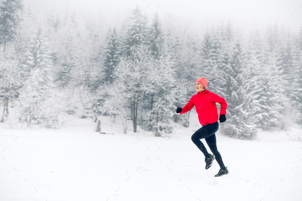 Happy girl running on snow in winter mountains - Stock Photo - Images