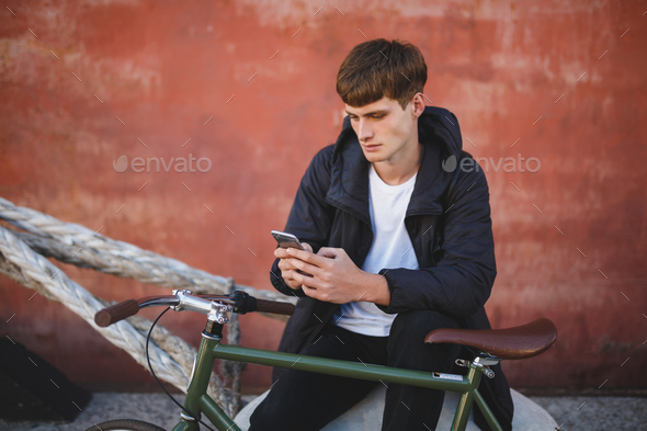 Young man in down jacket and white t-shirt sitting with mobile phone in hands and bicycle nearby - Stock Photo - Images