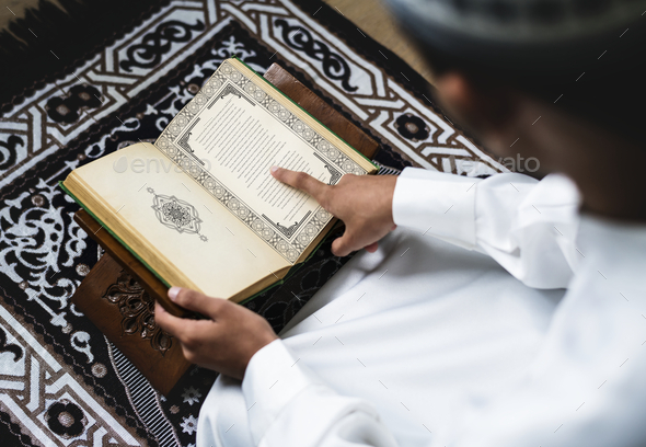 Muslim man studying The Quran - Stock Photo - Images