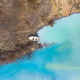 Aerial drone view of a boat in a turquoise lake contaminated with cyanide mining residuals - PhotoDune Item for Sale